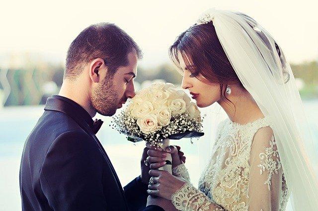 couple de mariés charmant avec un bouquet de fleurs