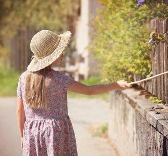 enfant devant sa clôture en bois
